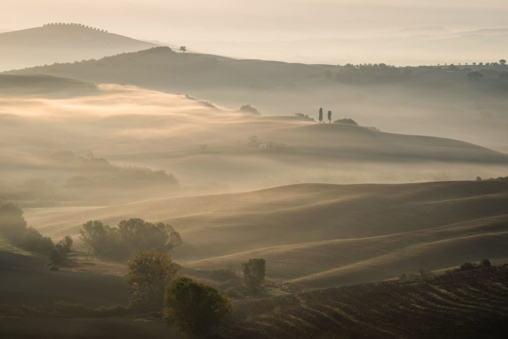 Glowing morning fog at Val d'Orcia with a Telephoto Lens